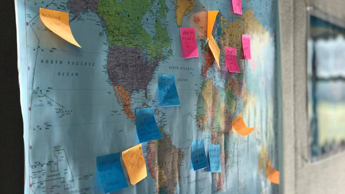 Interesting facts from around the world are marked on a map with post-it notes at the 2017 Spring Social.